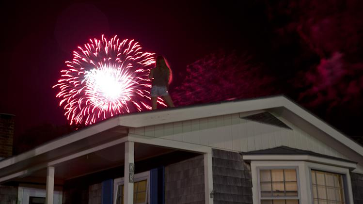 Juliette Bittner Farrissey, of Oak Bluffs, Mass., watches fireworks from a rooftop in Oak Bluffs, Mass., Friday, Aug. 22, 2014, on the island of Martha's Vineyard. President Barack Obama and his family watched the fireworks show as well with advisor Valerie Jarrett and friends, according to the White House. (AP Photo/Jacquelyn Martin)