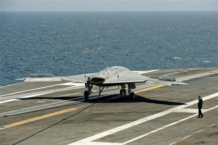 An X-47B pilot-less drone combat aircraft comes to a stop after landing on the deck of the USS George H.W. Bush off the coast of Norfolk
