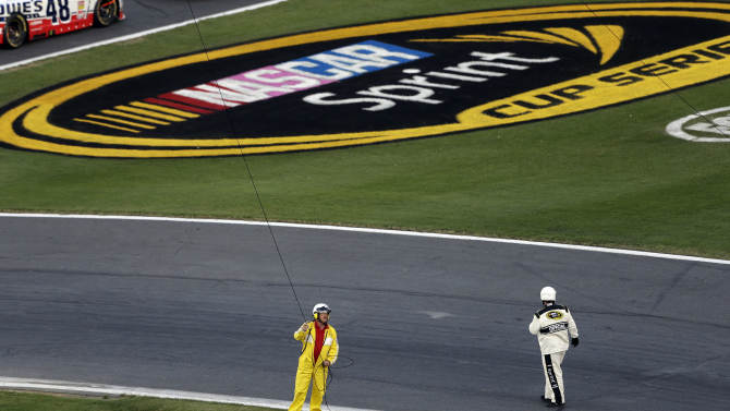 An official and a member of the cleanup crew attend to a broken television cable rig during a red flag in the NASCAR Sprint Cup Series Coca-Cola 600 auto race at Charlotte Motor Speedway in Concord, N.C., Sunday, May 26, 2013. Several cars were damaged by the broken rig. (AP Photo/Gerry Broome)