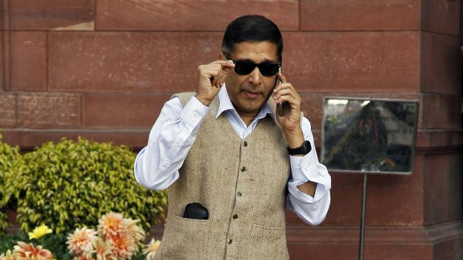 Chief economic adviser at India's Finance Ministry, Arvind Subramanian, speaks on a mobile phone outside his office ahead of the presentation of the 2015/16 federal budget in New Delhi