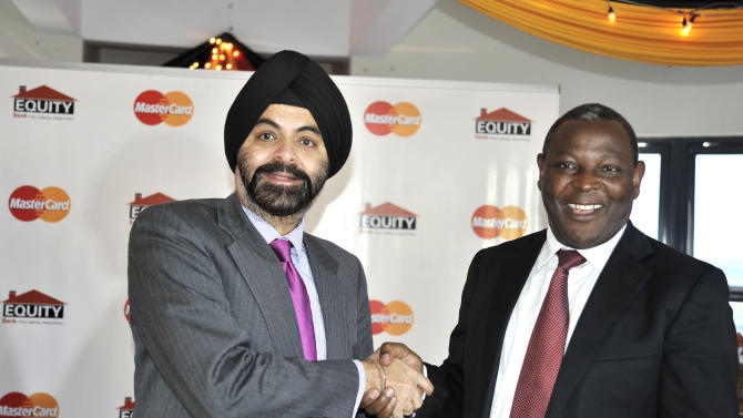 IMAGE DISTRIBUTED FOR MASTERCARD WORLDWIDE - Dr. James Mwangi (right), Equity Bank CEO, and Ajay Banga (left), MasterCard Worldwide President and CEO, celebrate an agreement between MasterCard and Equity Bank to issue five-million MasterCard PayPass debit, credit and prepaid cards over the next 18 months, at a signing ceremony in Nairobi, Kenya on Tuesday Jan. 15, 2013. The MasterCard cards with chip-enabled technology will be issued first into the Kenyan market and then extended into Uganda, Tanzania, Rwanda, and South Sudan. The initiative introduces MasterCard PayPass, with the first ever installation of PayPass enabled point of sale terminals across the region, and Mobile Point of Sale systems, which allows merchants to receive payments via low cost add-ons linked to secure applications on their mobile devices. In a move towards increasing financial inclusion in Kenya and East Africa at large, this program caters specifically to the unbanked and under-banked population, empowering African consumers to use electronic payments which provide a safe and secure way to pay versus cash and other forms of payment. (Riccardo Gangale /AP Images for Mastercard Worldwide)