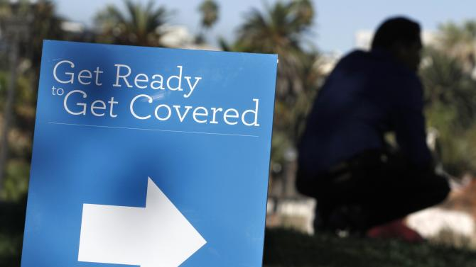 A man is silhouetted behind a sign at an Affordable Care Act outreach event hosted by Planned Parenthood for the Latino community in Los Angeles, California