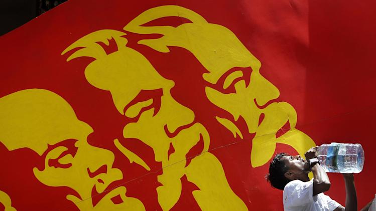An activist of Sri Lanka's Marxist political party, People's Liberation Front, drinks water from a bottle as a billboard of Communist leaders from left, Vladimir Lenin, Karl Marx and Friedrich Engels is displayed in the background during a street march to celebrate international Labor Day known as May Day in Colombo, Sri Lanka, Tuesday, May 1, 2012. May Day moved beyond its roots as an international workers' holiday to a day of international protest Tuesday, with rallies throughout Asia demanding wage increases and marches planned across Europe over government-imposed austerity measures. (AP Photo/Gemunu Amarasinghe)
