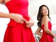 woman trying on red dress in dressing room