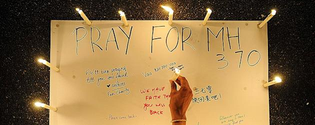 A woman places a lighted candle on a poster with messages expressing hope for passengers on Malaysia Airlines Flight MH370. (Reuters)