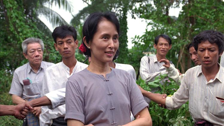 FILE - In this July 14, 1995 file photo, Nobel Peace Prize winner Aung San Suu Kyi is surrounded by bodyguards and aides in the garden of her house during a press conference following her release earlier in the week after six years under house arrest, Rangoon, Burma, Friday, July 14, 1995. Twenty-four years ago Aung San Suu Kyi left Europe for what was then a military-controlled nation called Burma. She returns Wednesday, June 13, 2012 the icon of Myanmar's democracy movement to a continent eager to hear from her whether the country's recent reforms truly spell the end of its cruel dictatorship.(AP Photo/Anat Givon, File)