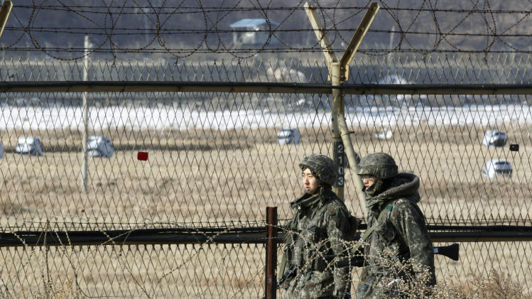 "South Korean army soldiers patrol along a barbed-wire fence in Paju, South Korea, near the demilitarized zone (DMZ) of Panmunjom, Sunday, Jan. 27, 2013.   North Korean leader Kim Jong Un convened top security and foreign affairs officials and ordered them to take ""substantial and high-profile important state measures,"" state media said Sunday, indicating that he plans to push forward with a threat to explode a nuclear device in defiance of the United Nations. (AP Photo/Ahn Young-joon)"