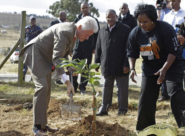 Former American president Bill Clinton, left, plants a tree to celebrate former South African president Nelson Mandela birthday in Qunu, South Africa, Tuesday, July 17, 2012. South African&#39;s will celebrate former president Nelson Mandela&#39;s birthday tomorrow. (AP Photo/Schalk van Zuydam)