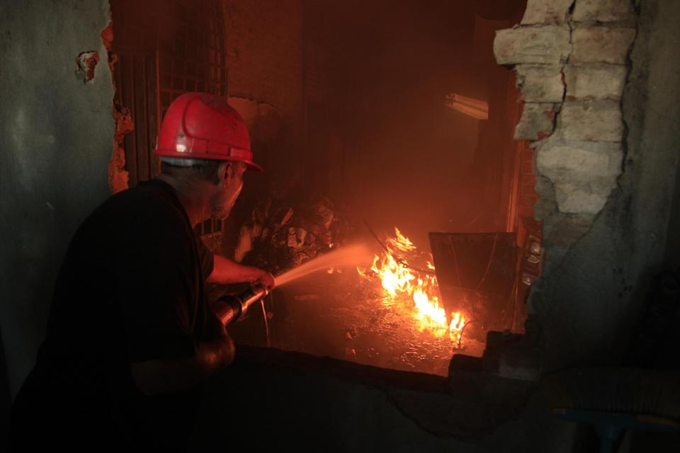 A Pakistani fireman tries to extinguish a factory fire on Tuesday, Sept. 11, 2012  in Lahore, Pakistan. A fire that broke out in a factory in eastern Pakistan on Tuesday after sparks from a generator hit chemicals used to make shoes killed dozens of  people, a Pakistani police officer said. (AP Photo/K.M. Chaudary)