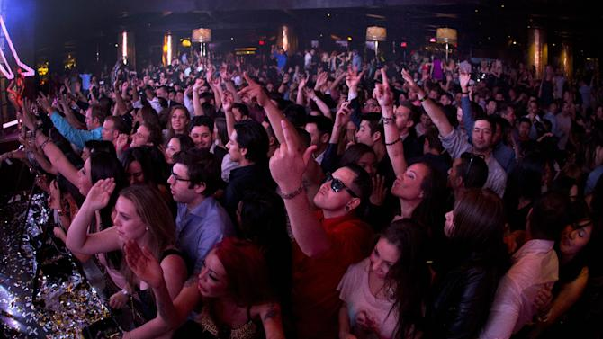 Revelers dance to the music played by DJ Afrojack inside the XS nightclub in Las Vegas on Sunday, Jan. 20, 2013. (AP Photo/Julie Jacobson)