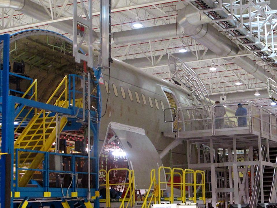 Workers assemble the middle section of Boeing's new 787 aircraft at the company's plant in North Charleston, S.C., on Friday, April 27, 2012. The company was rolling out the first of its new 787s manufactured at its South Carolina plant which opened last year. (AP Photo/Bruce Smith).