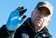 Louisiana Department of Wildlife and Fisheries Secretary Robert Barham holds up an oiled glove last January after finding deposits of oiled marsh land near Bay Jimmy. British oil giant BP was temporarily banned by the US Environmental Protection Agency from US government contracts on Wednesday due to its behavior in the April 2010 Gulf of Mexico oil disaster