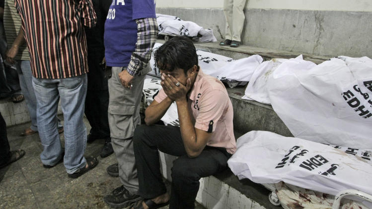 A Pakistani man, reacts next to the body of a relative who was killed in a bomb blast, at a hospital's morgue in Karachi, Pakistan, Sunday, March 3, 2013. Pakistani officials say a bomb blast has killed dozens of people in a neighborhood dominated by Shiite Muslims in the southern city of Karachi. (AP Photo/Fareed Khan)