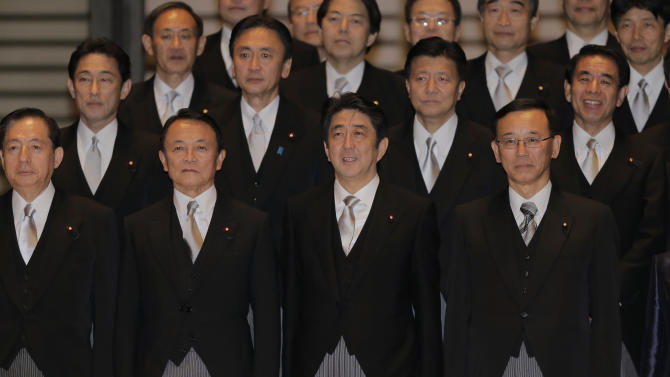 Japan's new Prime Minister Shinzo Abe, front row second right, and his Cabinet members, front row from left, Land, Infrastructure, Transport and Tourism Minister Akihiro Ota, Finance and Deputy Prime Minister Taro Aso, Justice Minister Sadakazu Tanigaki, front row right, and others pose for a group photo after attending an attestation ceremony for his Cabinet at the Imperial Palace in Tokyo Wednesday, Dec. 26, 2012. Old-guard veteran Abe was voted back into office as prime minister Wednesday and immediately named a new Cabinet, ending three years of liberal administrations and restoring power to his conservative, pro-big-business party that has run Japan for most of the post-World War II era. (AP Photo/Itsuo Inouye)