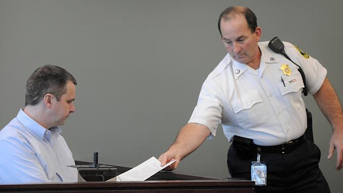 A court officers hands Thomas Mortimer IV a document during his hearing at Middlesex Superior Court in Woburn, Mass., Wednesday Oct. 3, 2012. Mortimer plead guilty to the first-degree murder of his wife, mother-in-law and two young children after an argument over a bounced check.  He was sentenced to life in prison without the possibility of parole. (AP Photo/Boston Herald, Patrick Whittemore, POOL)