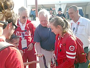 Rosie MacLennan showing her Olympic gold medal in trampoline to father John and longtime coach Dave Ross just after leaving the Greenwich Arena on Saturday, August 4th.