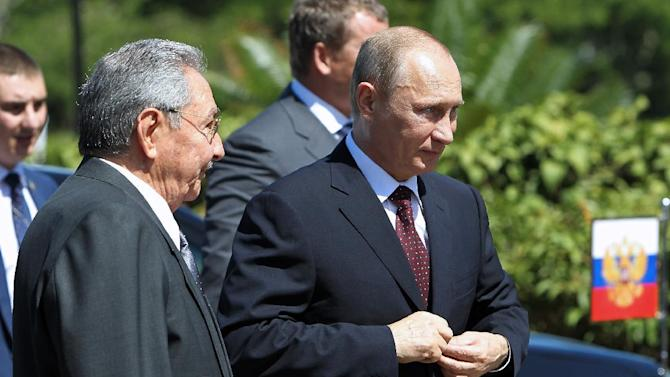 Russian President Vladimir Putin (R) and Cuban President Raul Castro attend a wreath-laying ceremony at the Soviet Soldier Monument in Havana on July 11, 2014