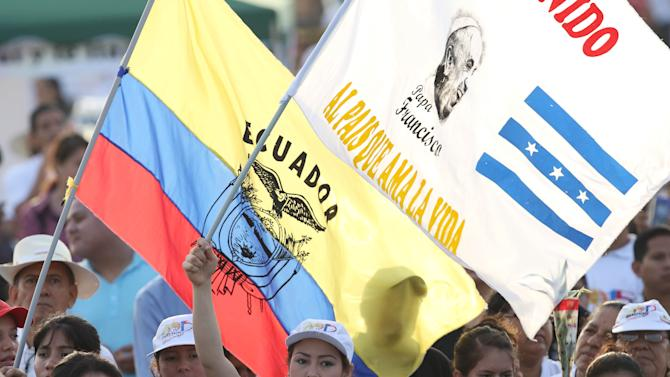 """A woman holds up a banner with a message that reads in Spanish; """"Welcome Pope Francis, to the country that loves life,"""" alongside an Ecuadorian national flag, in a group of thousands waiting in the Samanes Park where the pope is expected to celebrate Mass with up to 1 million people, in Guayaquil, Ecuador, Monday, July 6, 2015. Francis is taking it relatively easy on his first full day in Ecuador, making the quick flight to Guayaquil for the Mass and then a lunch with a group of fellow Jesuits.  (AP Photo/Fernando Vergara)"""