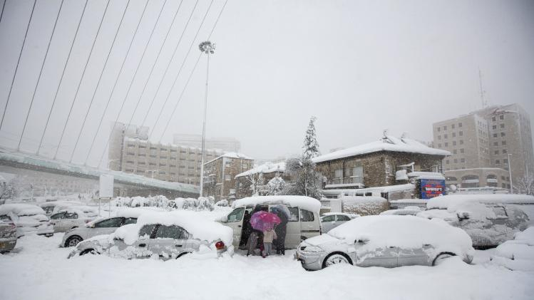 People leave their car during a snowstorm after it was stuck in heavy snowfall in Jerusalem