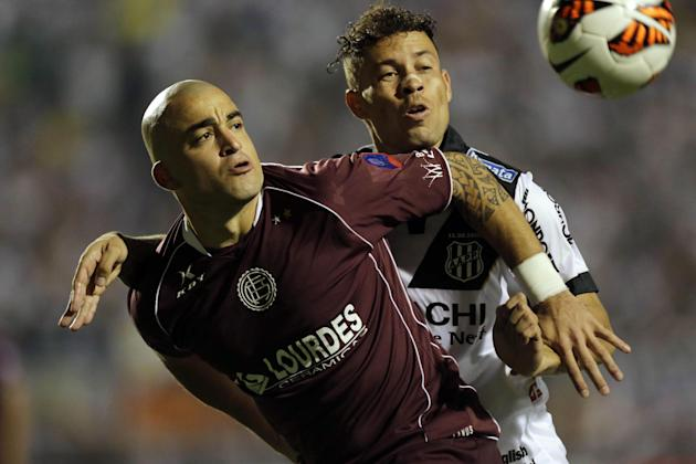 Baraka of Brazil's Ponte Preta, right, and Santiago Silva of Argentina's Lanus fight for the ball during the first leg match of Copa Sudamericana final in Sao Paulo, Brazil, Wednesday, Dec. 4,