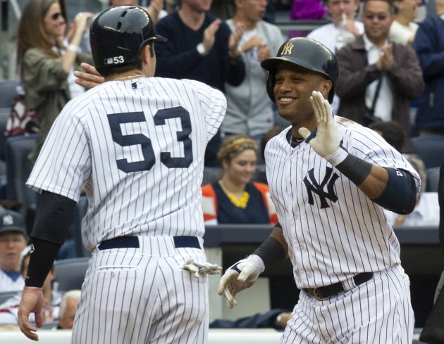 New York Yankees batter Cano celebrates with runner Romine after he hit a second two-run home run against the Toronto Blue Jays in the fifth inning of their MLB American League game in New York