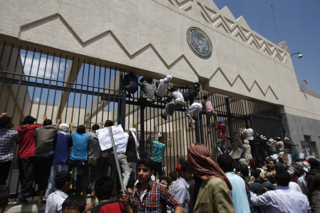 FILE - In this Thursday, Sept. 13, 2012 file photo, Yemeni protestors climb the gate of the U.S. Embassy during a protest about a film ridiculing Islam's Prophet Muhammad, in Sanaa, Yemen. A drive-by shooting that killed a top Yemeni security official who worked at the U.S. Embassy in Sanaa Thursday, Oct. 11, 2012 raises concern that al-Qaida militants here are bouncing back and getting bolder after suffering defeats this year in U.S.-Yemeni military offensive. Al-Qaida has carried out a string of assassinations of top government and military officials, reportedly has a hit list to kill more and has called for attacks on U.S. diplomatic missions.(AP Photo/Hani Mohammed, File)