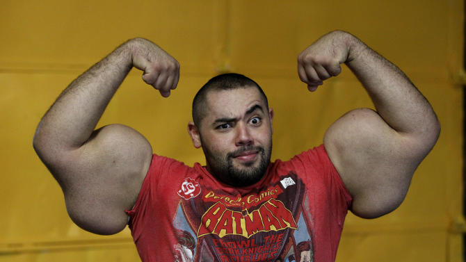 In this photo taken, Friday, Nov. 16, 2012, Egyptian Body builder Moustafa Ismail poses during his daily workout at World Gym in Milford, Mass. Ismail has been given the title of world's biggest arms, biceps and triceps, by the Guinness Book of World Records. (AP Photo/Stephan Savoia)