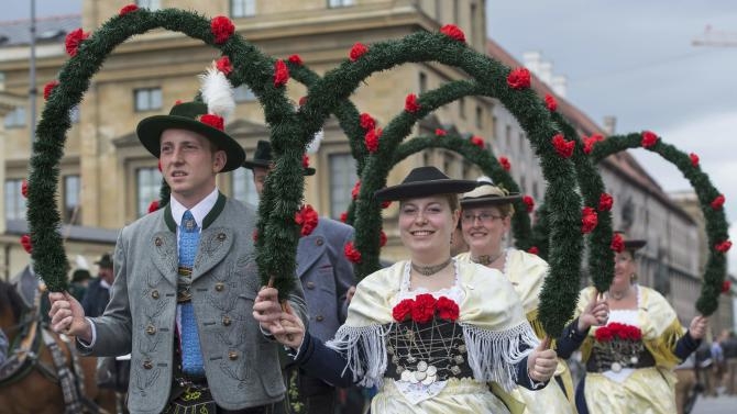 People dressed in traditional Bavarian clothes take part in the Oktoberfest parade in Munich
