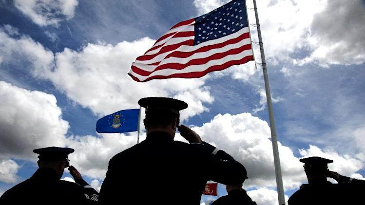 Members of the 560th Air Force Band/Air Natioanl Guard of the Northwest, including, from left,  Senior Master Sgt. Michael Baker, Tech Sgt. David Volland, Major James Phillips, Master Sgt. Jaye Nordling salute the flag during the National Anthem during the 3rd annual Memorial Day Ceremony at the Washington State Veterans Cemetery in Medical Lake, Wash. on Monday, May 27, 2013. (AP Photo/The Spokesman-Review, Dan Pelle)  COEUR D'ALENE PRESS OUT