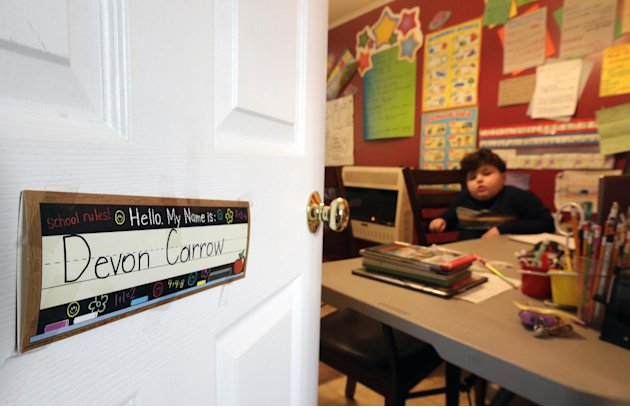 In this Tuesday, Jan. 22, 2013 photo, Devon Carrow attends school from home while operating a robot in the classroom, in Orchard Park N.Y. Carrow's life-threatening allergies don't allow him to go to 