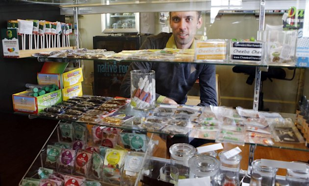 "This Thursday, April 11, 2013, photo shows Matt Brown, co-owner of Denver's new ""My 420 Tours,"" looking over a sampling of marijuana edibles at a dispensary in Denver. ""My 420 Tours,"" gives traveling pot users everything but the drug. Brown has sold 160 tour packages to visiting pot smokers for the April 20 weekend. Prices start at $499, not including hotel or air. Instead, the service plans to pick up marijuana tourists at the airport in limousines, escort them to Cannabis Cup and other Denver-area marijuana celebrations and take them to a cannabis-friendly hotel (a national chain that has given permission for Denver patrons to smoke marijuana on outdoor patios but doesn't want its name advertised). (AP Photo/Ed Andrieski)"