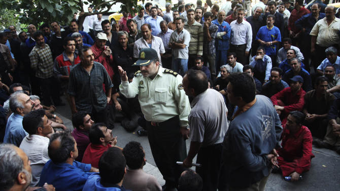 In this Tuesday, Aug. 14, 2012 photo, a police colonel, center, talks with a group of Iranian workers during their protest in front of the Industrial Ministry building in Tehran, Iran, demanding their delayed salaries. For weeks, a manifesto complaining about Iran's sinking economy circulated in secret among factories and workshops. In the end, some 10,000 signatures were on a petition addressed to Iran's labor minister calling attention to the street-level fallout from Western sanctions: rising prices, fewer jobs. (AP Photo)