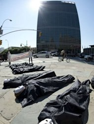 Protesters lay on the sidewalk in body bags on July 2, near the United Nations in New York. Three weeks of UN talks aimed at hammering out a draft treaty to regulate the $70 billion a year global arms trade finally got under way on Tuesday, a day late because of a diplomatic tussle over Palestinian representation
