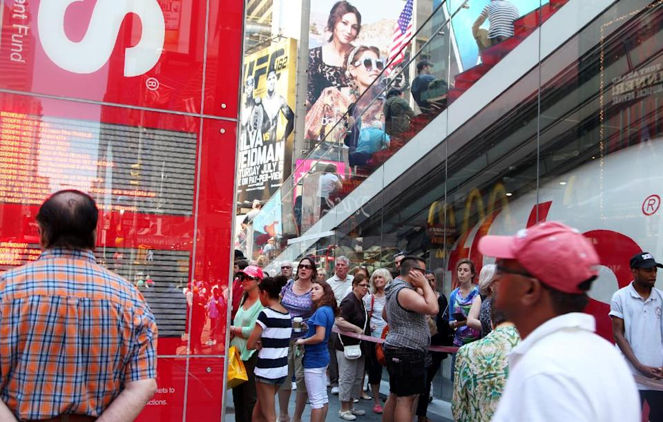 This June 19, 2013 photo shows crowds gathering outside the TKTS booth in Times Square in New York. The booth, which offers same-day discount Broadway and off-Broadway tickets, turns 40 this summer. (AP Photo/Mark Kennedy)