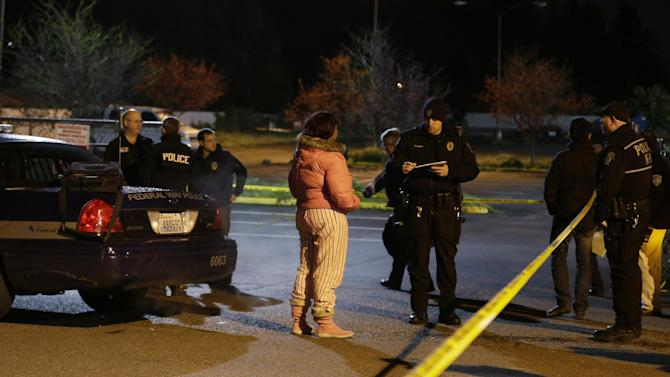 Police officers interview a woman who told reporters she heard gunshots at the scene of an overnight shooting that left five people dead, Monday, April 22, 2013, at an apartment complex in Federal Way, Wash. (AP Photo/Ted S. Warren)