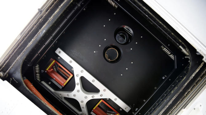 The camera lens and other sensors are visible through the hole in the bottom of the King Air plane before a National Oceanic and Atmospheric Administration flight to document coastal changes after Superstorm Sandy, Thursday, Nov. 1, 2012. (AP Photo/Alex Brandon)