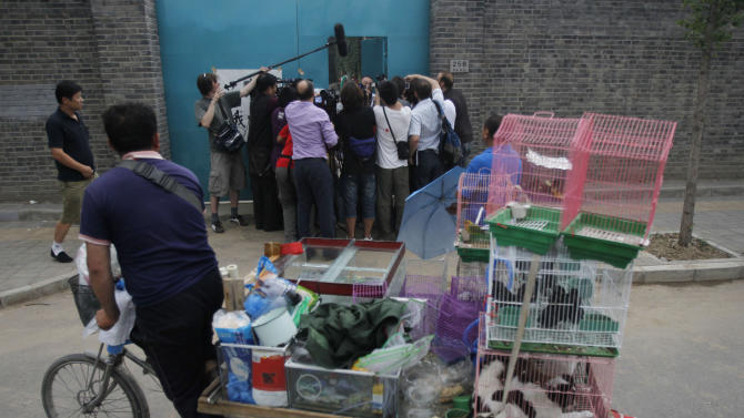 A street vendor selling birds and dogs watches activist artist Ai Weiwei who is surrounded by journalists gathered outside his home in Beijing, China, Thursday, June 23, 2011. Ai, the most high-profile target of a sweeping crackdown on activists in China, has returned home late Wednesday after nearly three months in detention. (AP Photo/Ng Han Guan)
