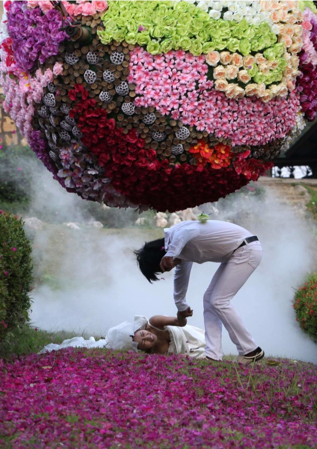 Thai bride Chutima Imsuntear falls as she runs with groom Sopon Sapaotong during a wedding ceremony in Prachin Buri province