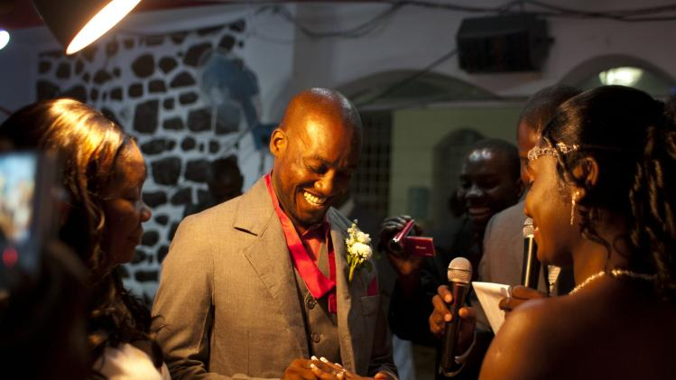 In this July 20, 2012 photo, professional dancer Georges Exantus puts a ring on the finger of his bride Sherly Henrisme Exantus at their wedding in Port-au-Prince, Haiti. Exantus thought he'd never dance again. The earthquake three years ago in Haiti's capital flattened the apartment where he was living, where he spent three days trapped under a heap of jagged rubble. After friends dug him out, doctors amputated his right leg just below the knee. Three years later, the 32-year-old professional dancer is back on the floor, spinning away as he does the salsa, cha-cha and samba. A prosthetic leg doesn't hold him back. Exantus says he's the same person he was before the Jan. 12, 2010, earthquake struck southern Haiti. (AP Photo/Dieu Nalio Chery)