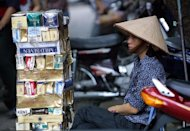 A cigarettes vendor is seen behind a pile of empty cartons of foreign and local cigarette brands, in Hanoi. Vietnam has passed a law banning smoking in public places and all tobacco advertising, according to an official