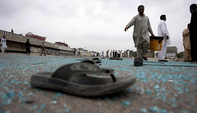 Pakistani security officials examine the site of a bomb attack in Karachi, Pakistan on Wednesday, July 11, 2012. A bomb planted on a cycle and detonated using remote control targeted a bus carrying government employees of Pakistan Space and Upper Atmosphere Research Commission, police said. (AP Photo/Fareed Khan)