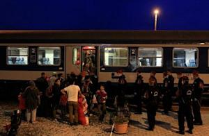 Migrants enter a train at a train station in Magya…