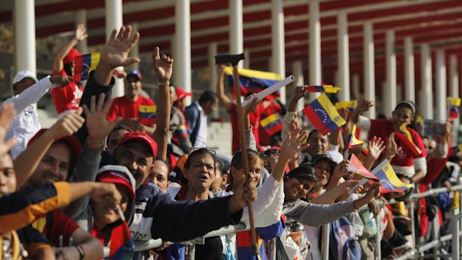 People lining up to see the body of Venezuela's late President Hugo Chavez cheer outside the military academy where he is lying in state in Caracas, Venezuela on Saturday, March 9, 2013. Chavez died on March 5, 2013 after a nearly two-year bout with cancer. He was 58. (AP Photo/Rodrigo Abd)