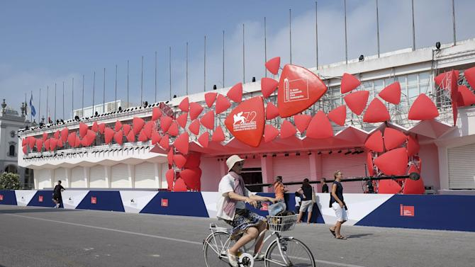 A woman rides a bicycle past the entrance of the venue for the 72nd Venice Film Festival