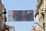 A giant photograph showing French singer and actor Johnny Hallyday kissing his wife Laetitia hangs between buildings, on May 12 in Cannes, southeastern France. Arthouse directors and Hollywood royalty will converge on the French Riviera for two weeks from Wednesday as the Cannes Film Festival rolls out the red carpet for the giants and mavericks of the movie galaxy