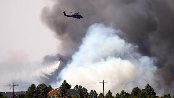 A helicopter from Ft. Carson's 4th Combat Aviation Brigade drops water behind a home and between advancing flames as the Black Forest Fire burns out of control for a second straight day near Colorado Springs, Colo. on Wednesday, June 12, 2013. Three Colorado wildfires fueled by hot temperatures, gusty winds and thick, bone-dry forests have together burned dozens of homes and led to the evacuation of more than 7,000 residents and nearly 1,000 inmates at medium-security prison. (AP Photo/Bryan Oller)