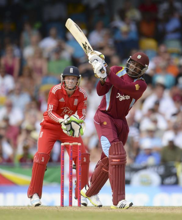 West Indies' Gayle hits a six watched by England's Buttler during the first T20 international at Kensington Oval in Bridgetown
