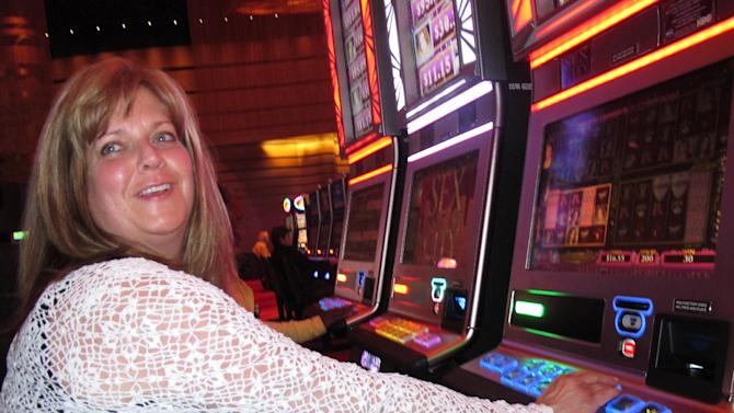 """FILE - In this May 21, 2012 file photo, Donna Kiddie of Point Pleasant Beach N.J. plays a """"Sex And The City"""" slot machine at Revel in Atlantic City N.J. Revel, which is in federal bankruptcy court, posted a $110 million operating loss in the nine months it was open in 2012. Atlantic City's 12 casinos collectively posted a $360 million operating profit last year, down 27.5 percent from 2011. (AP Photo/Wayne Parry, File)"""