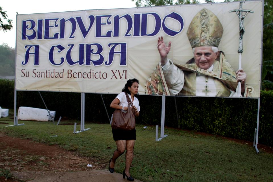 A woman walks past a sign welcoming Pope Benedict XVI to Cuba in Havana, Cuba, early Monday March 26, 2012.  Pope Benedict XVI arrives to Cuba on Monday afternoon. (AP Photo/Franklin Reyes)