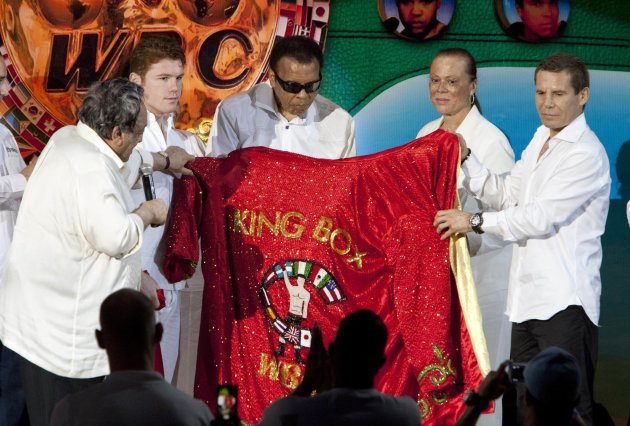 "The president of the WBC Jose Sulaiman, along with Mexican boxer Saul ""Canelo"" Alvarez and former Mexican boxer Julio Cesar Chavez, deliver a boxing robe to former U.S. boxer Muhammad Ali, during the"